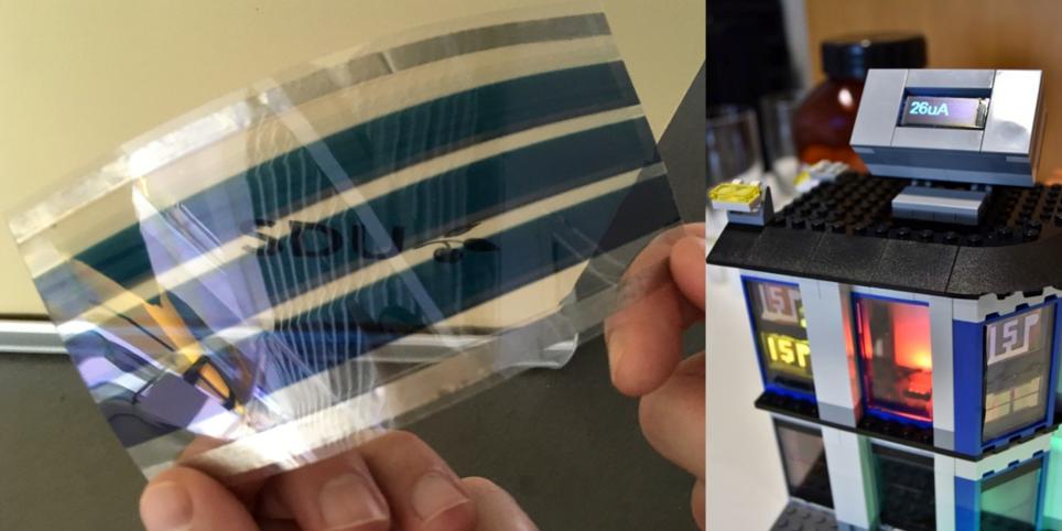 Links im Bild sieht man zwei Daumen/Finger, die ein längliches Modell einer Solarzelle mit verbesserten Kontakten hält; rechts das LEGO Modellhaus mit fensterintegrierten Solarzellen, einem Energiezähler auf dem Dach und leuchtenden OLED Lettern.